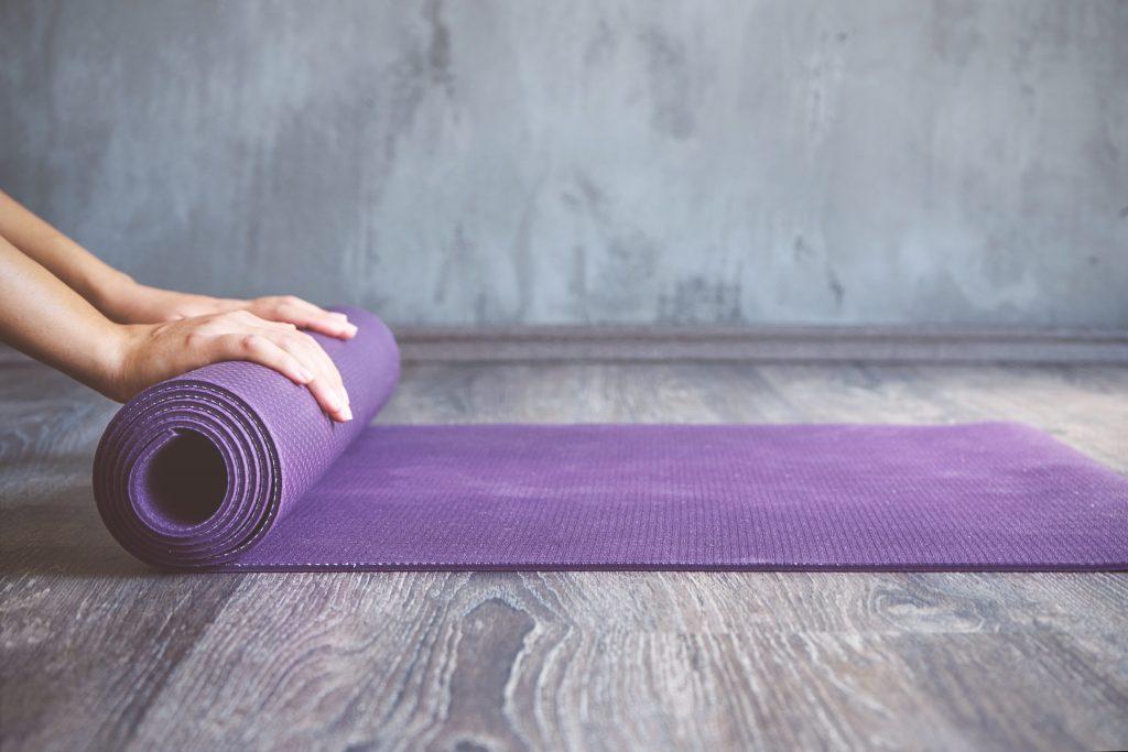Rolling up a purple yoga mat