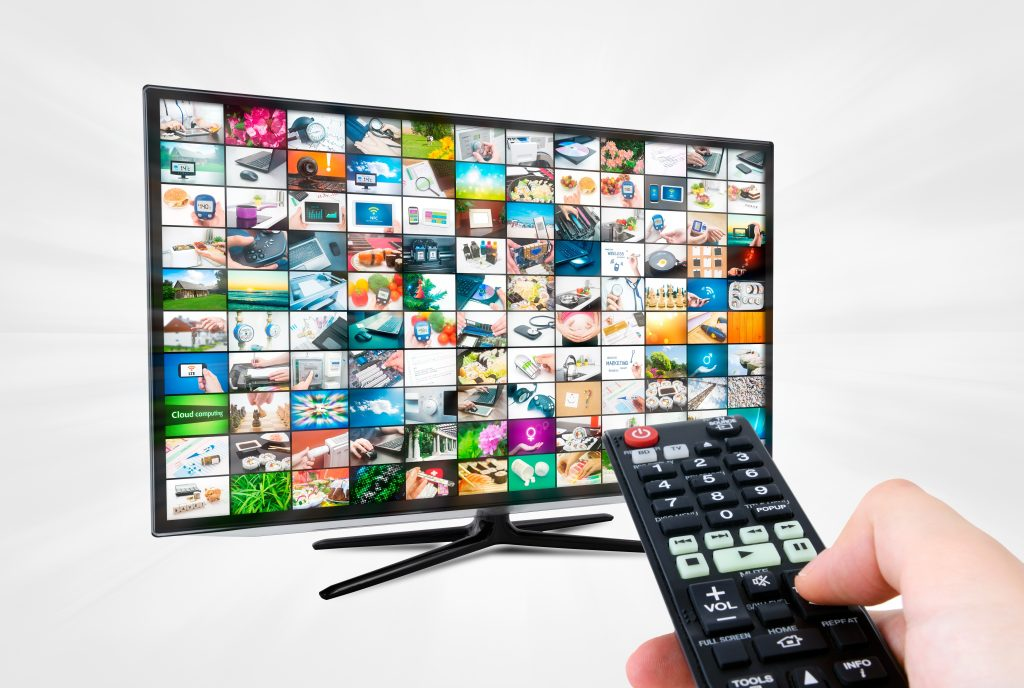 tv with hand holding remote