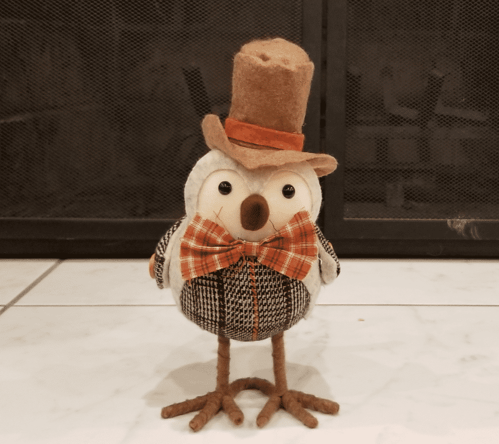 Small bird figure with top hat and fall colored bow tie