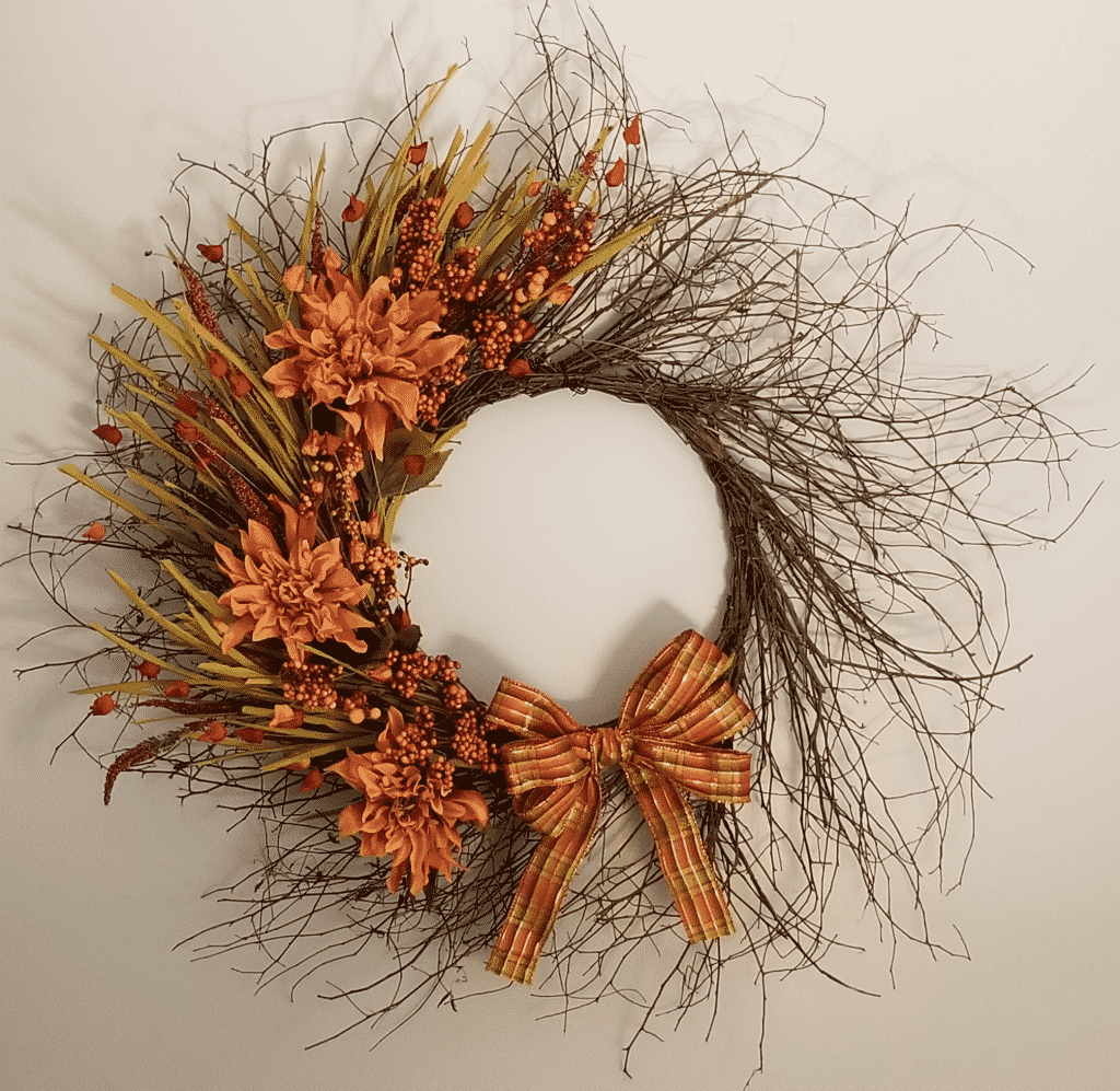 Wispy grapevine wreath with dahlias, berries, and bow
