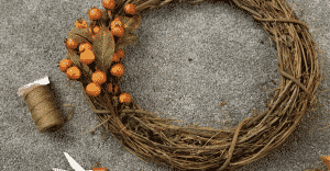 grapevine wreath with two sprigs of berries and string