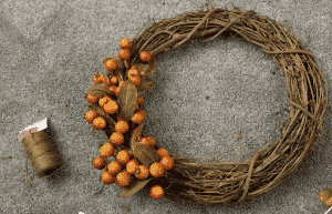 grapevine wreath with three sprigs of berries and string