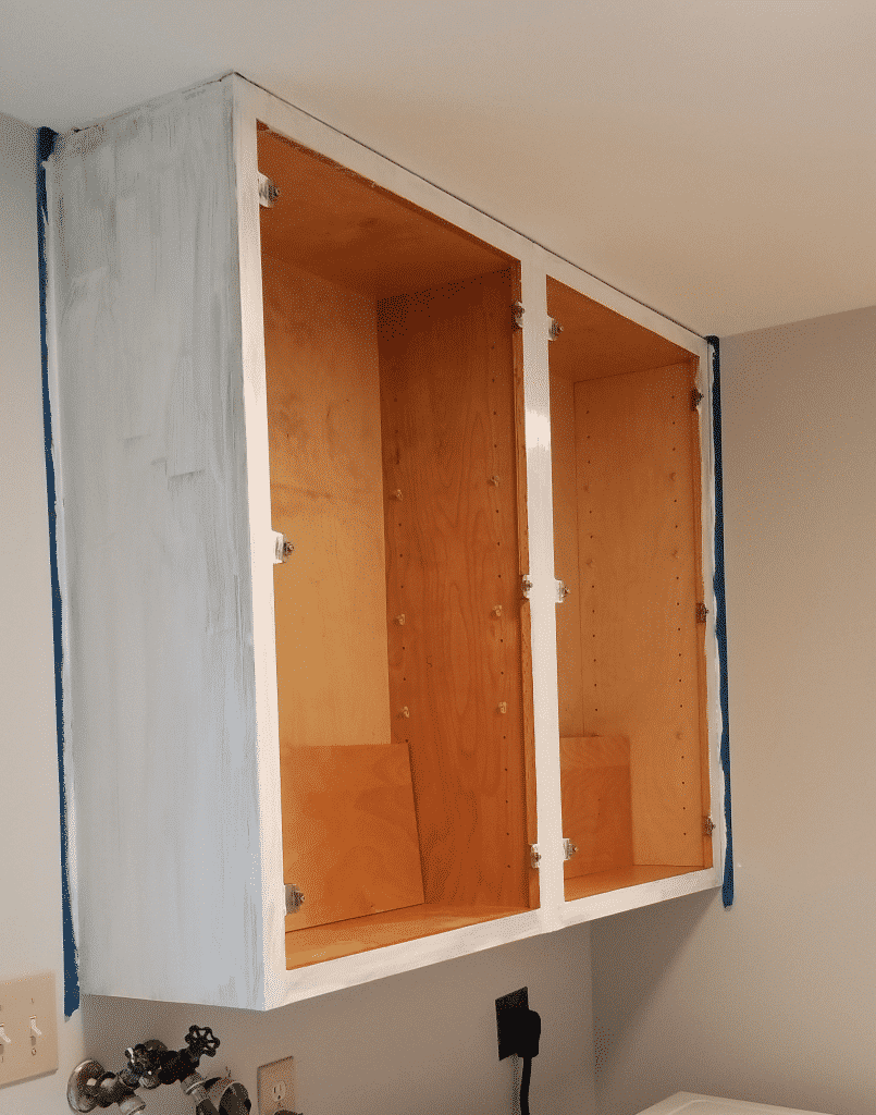 cabinets on the wall with one coat of paint