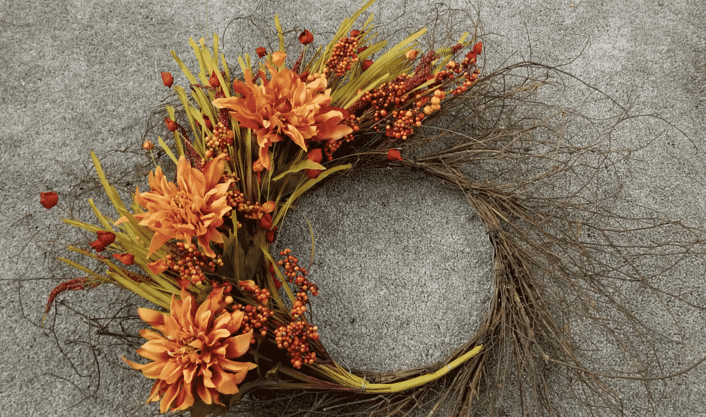 wispy grapevine wreath with flower stems, berries, and dahlias