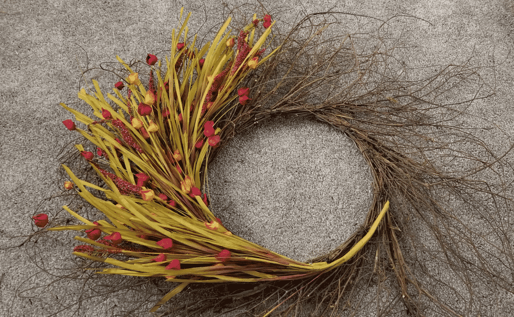 wispy grapevine wreath with multiple stems of flowers attached with wire