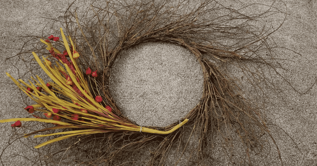 wispy grapevine wreath with one stem of flowers attached with wire