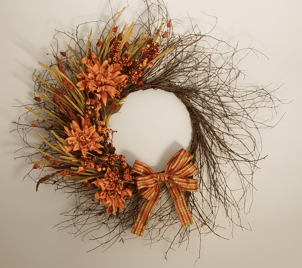 Completed wispy grapevine wreath with flower stems, berries, dahlias, and ribbon on wall