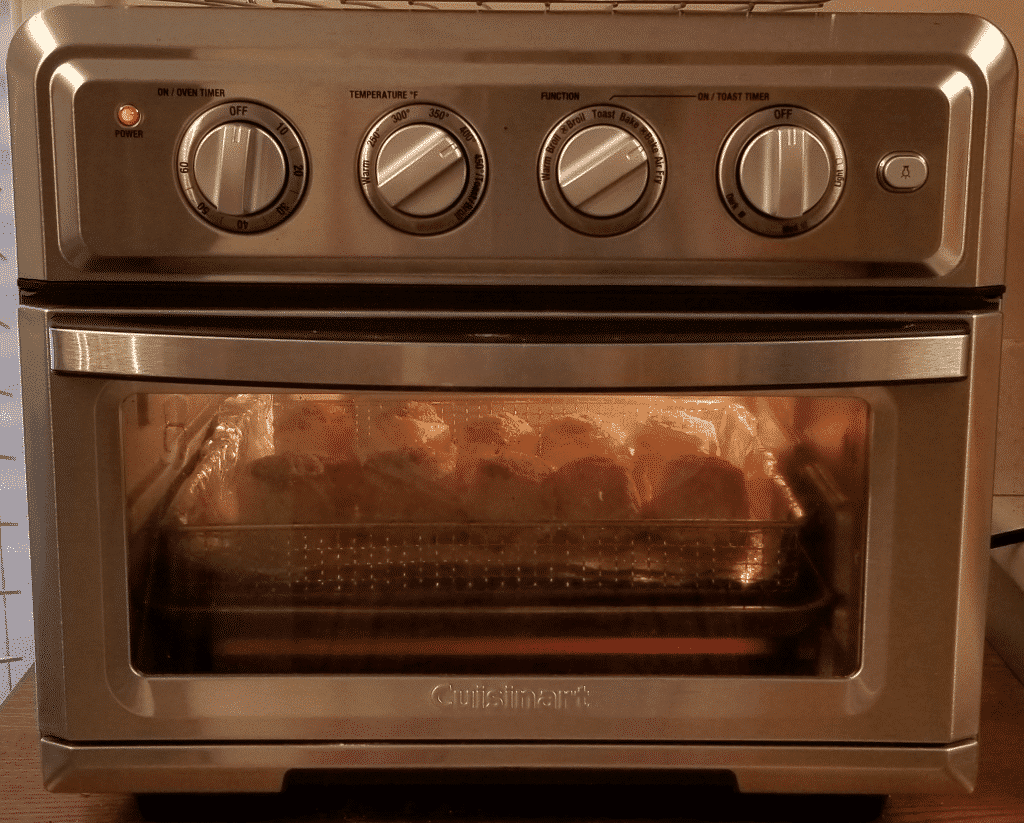 cinnamon rolls rising and expanding while baking in convection oven