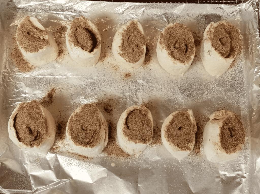 cinnamon rolls on prepared baking pan with ICBINB spray and cinnamon sugar