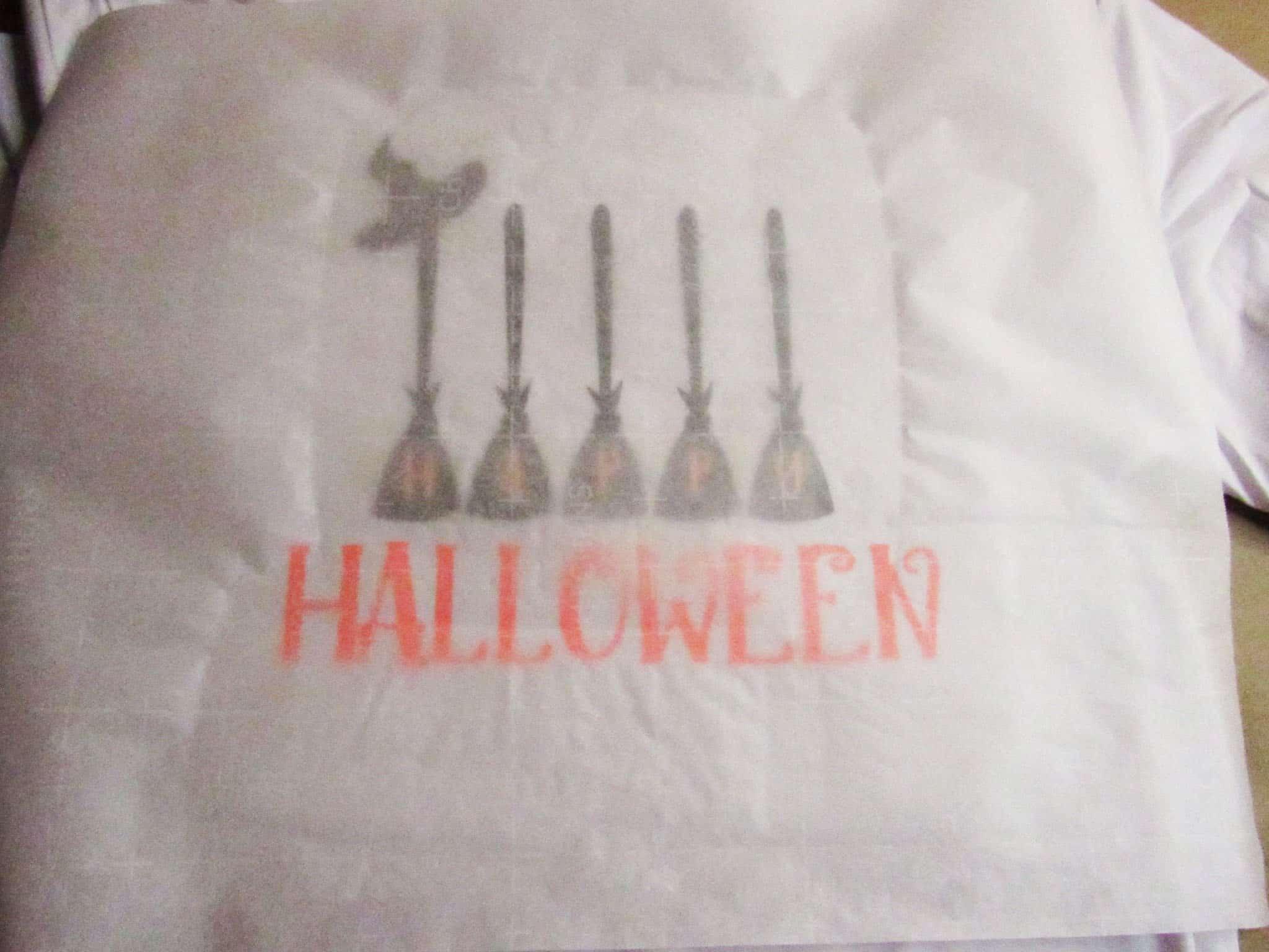 Ironing on final layer of DIY Happy Halloween t-shirt