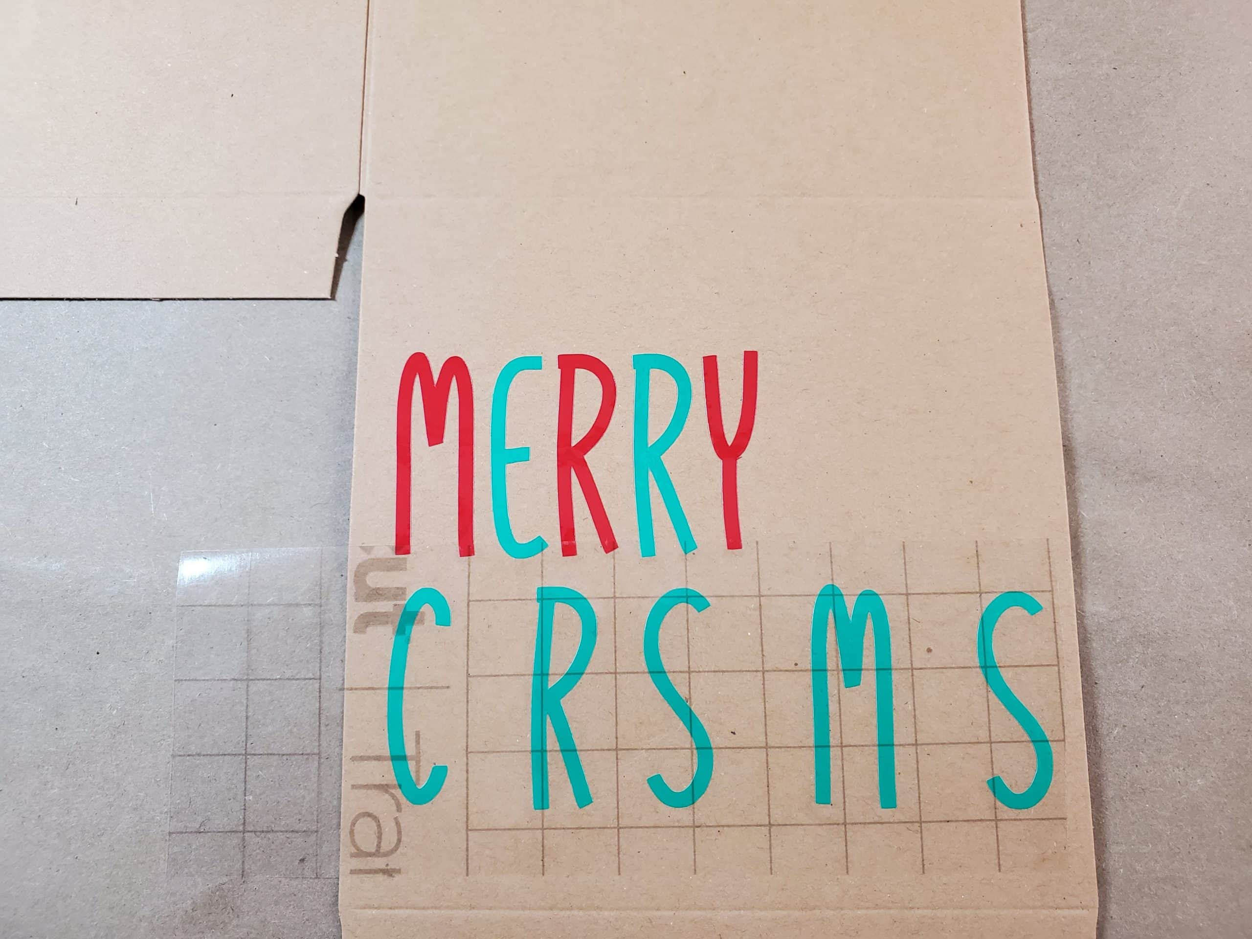 Attaching the green C R S M S lettering in Christmas with transfer tape